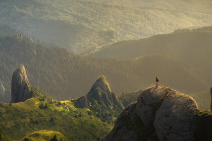 Person standing on a cliff in the mountains